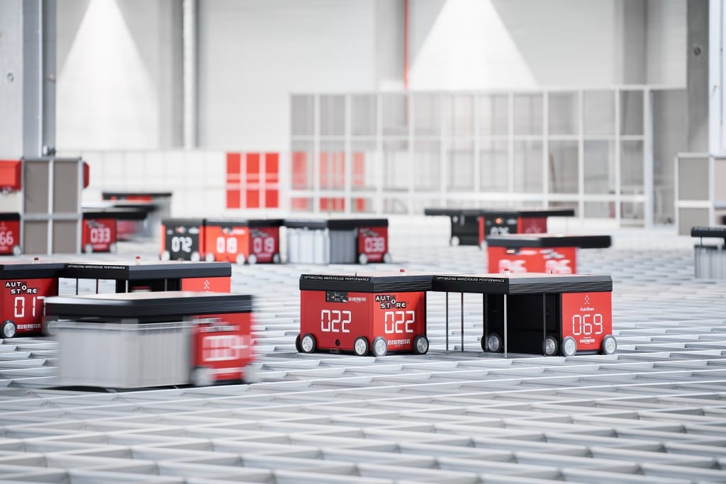Several AutoStore red line robots moving fast on a grid